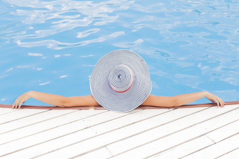 vrouw in zwembad met zonnehoed vakantie